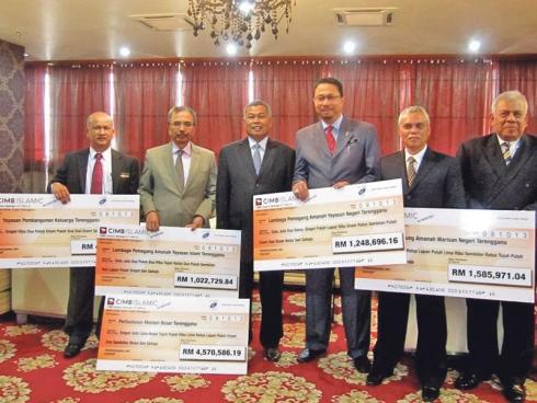 Ghazali beramah mesra bersama penerima Netbook 1Malaysia yang turut diperhatikan Alias (kiri).